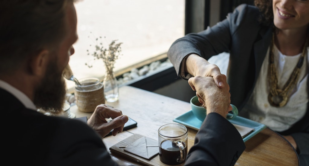 Two business people shaking hands over coffee table